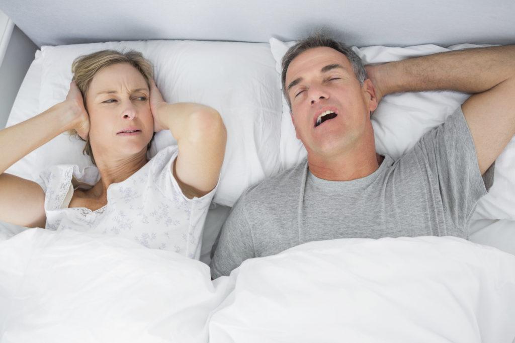 man snoring next to unhappy woman