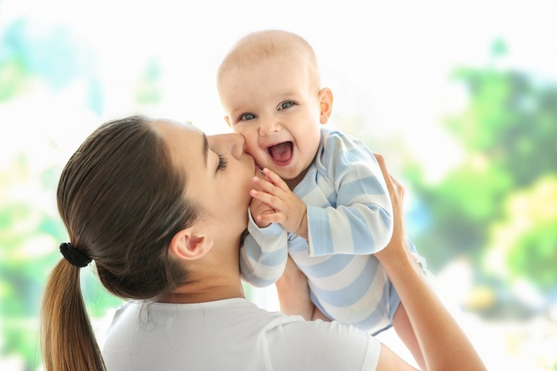 a woman holding up her baby and kissing it on the cheek