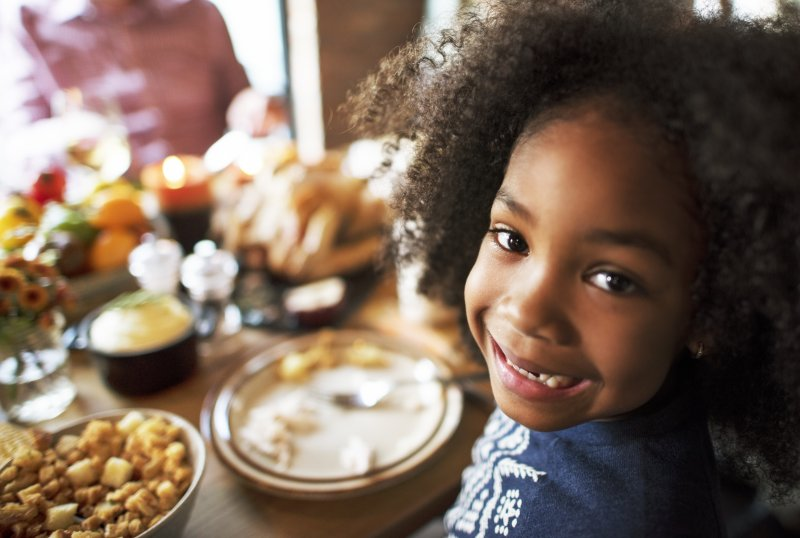 a young girl smiling at the Thanksgiving table