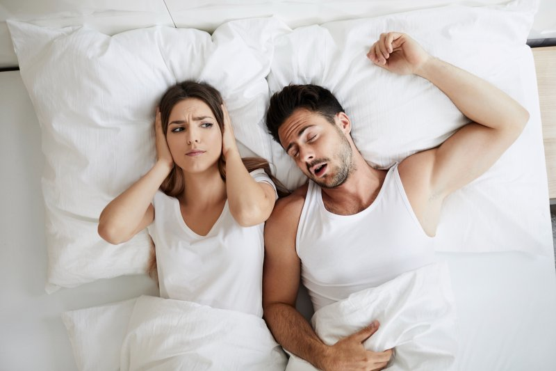 a man asleep with a woman putting her hands over her ears