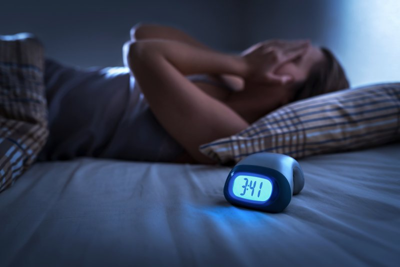 a woman lying in bed with her hands over her face and an alarm clock reading 3:41 a.m.