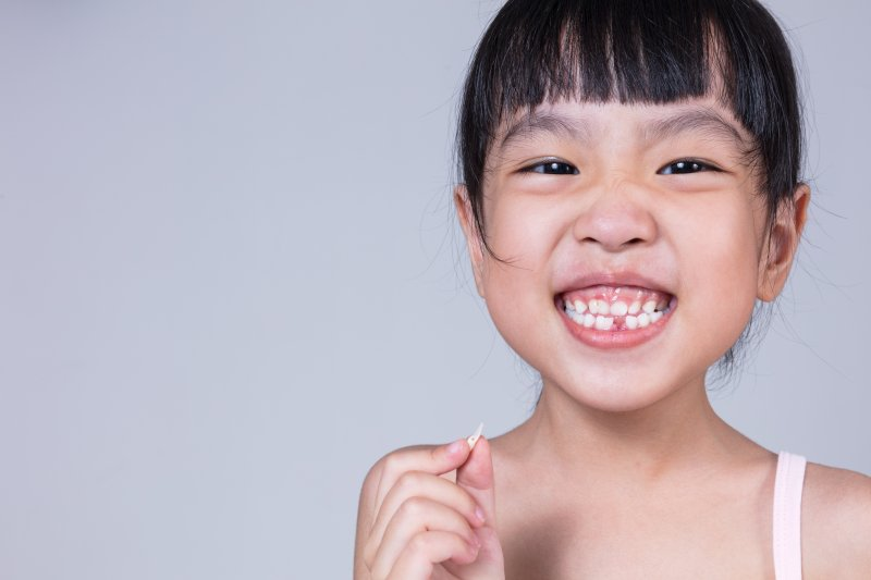 a little girl smiling wide while holding a tooth she recently lost