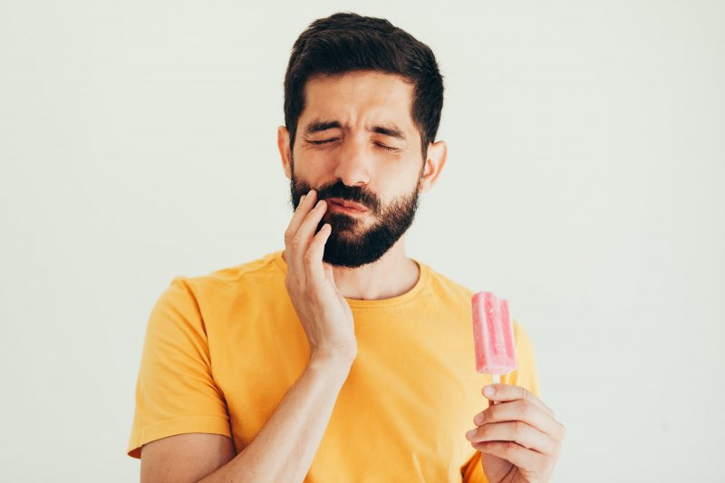 a man with a beard holding a popsicle while touching his cheek and wincing in pain because of a sensitive tooth