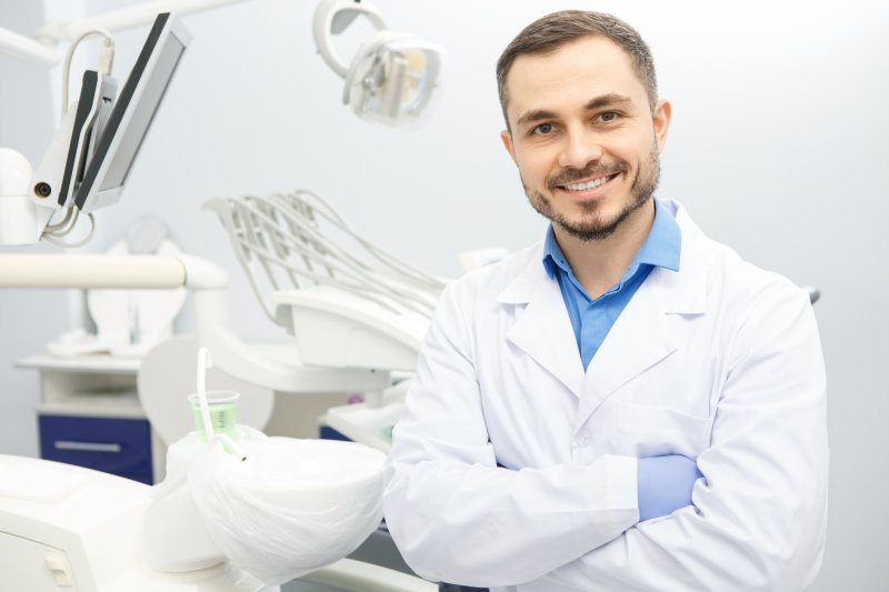 a male dentist wearing a lab coat and gloves while standing in a dental treatment room