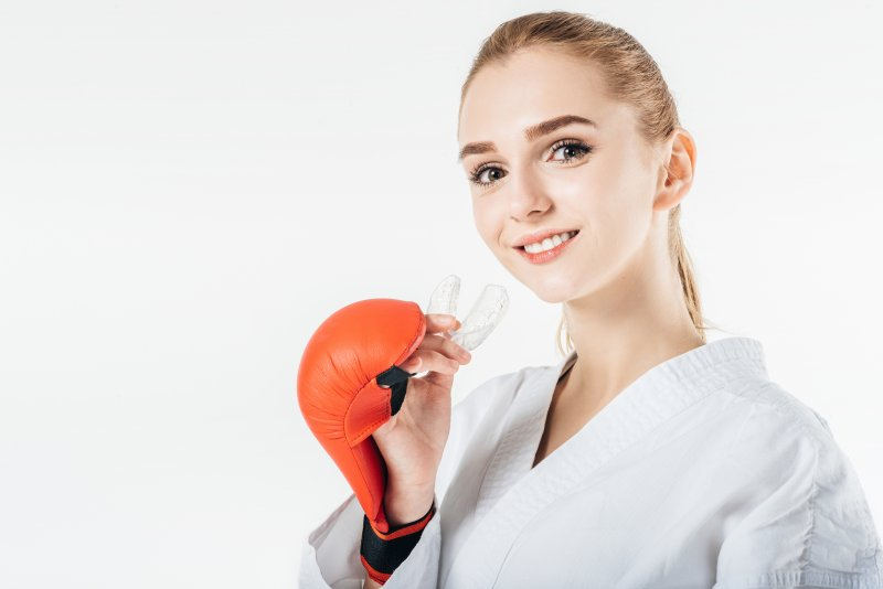 a young girl wears a karate robe and boxing glove while preparing to insert a mouthguard